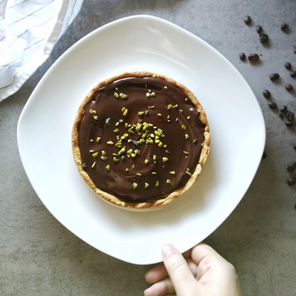 Veganer Kaffee-Schokoladen-Kuchen. In der linken Bildhälfte ist der Kuchen, getoppt mit einer cremigen Schokoladenganache und Pistazien, zu sehen. Rechts liegen auf dem grauen Untergrund Kaffeebohnen.