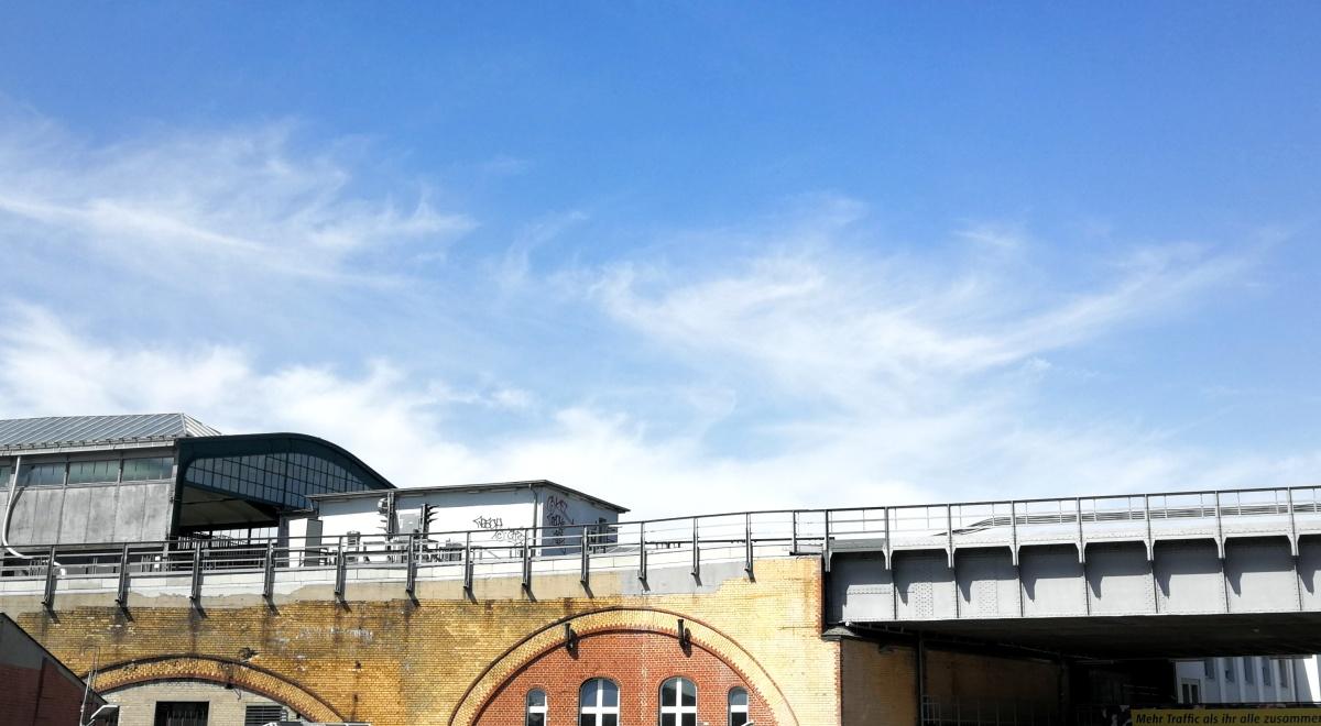 Ein Bild einer Berline Straßenbahnstation. Das Gebäude sieht industriell aus und der Himmel strahlt blau über der Station.