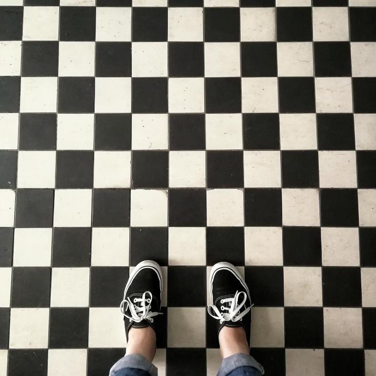 Ein schwarz-weiß gekachelter Fliesboden. Am unteren Bildrand sind mittag zwei Füße zu sehen.