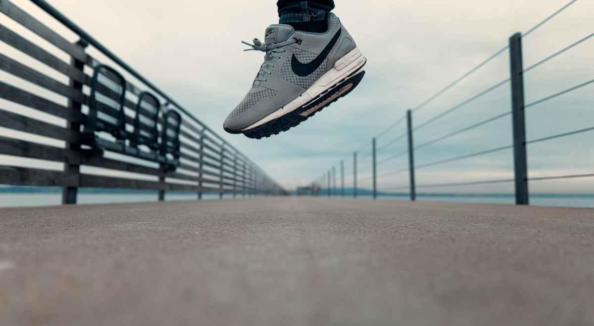 Ein Foto aus der Froschperspektive: Das Blickfeld liegt auf dem graubeigen Asphaltuntergrund, im Hintergrund sind blaue Gewässer zu sein. Im Fokus stehen die grauen Schuhe der Marke Nike, die eine hochspringende Person.trägt
