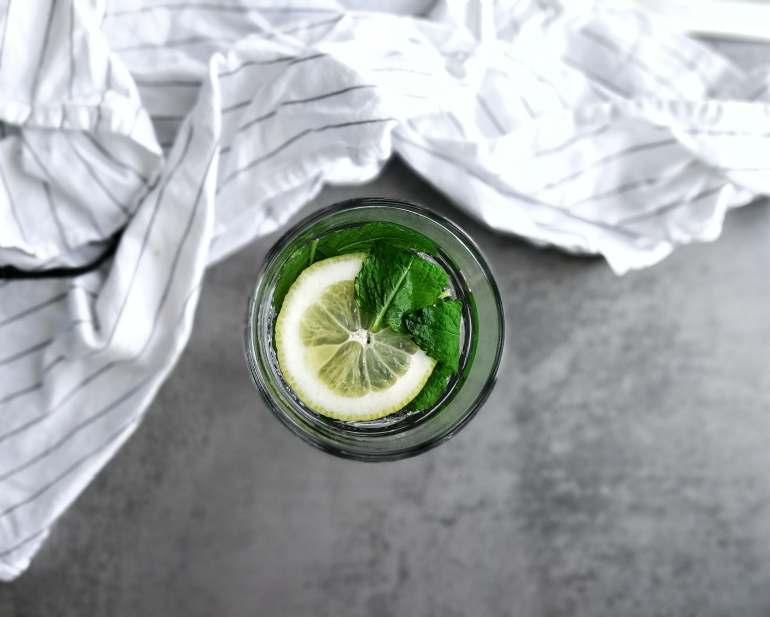 Ein Glas auf grauem Grund von oben fotografiert. Eine Zitronenscheibe und Minzblätter sind in dem Glas mit heißem Wasser aufgegossen. Im Hintergrund ein weißes Geschirrtuch.