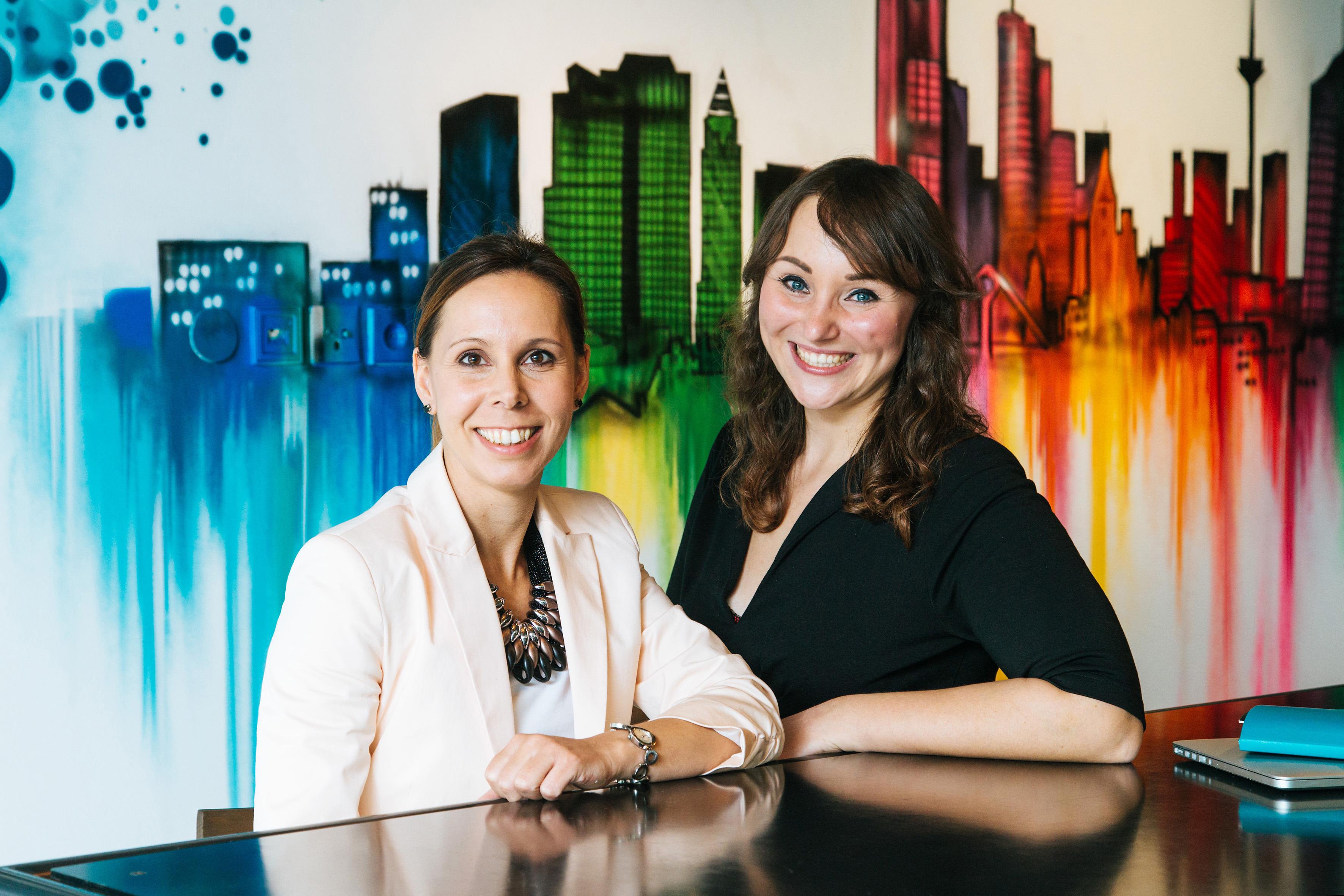 Zwei dunkelhaarige Frau lehnen an einen Tisch und blicken frontal lächelnd in die Kamera. Hinter ihnen ein buntes Graffiti der Frankfurter Skyline.