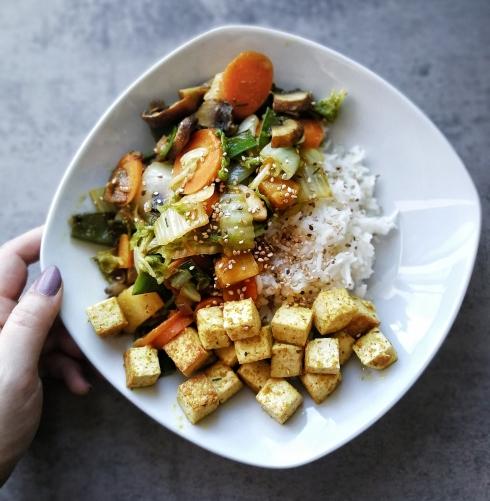 Ein Teller von oben fotografiert. Diverse Gemüsesorten wie Möhren und Pilze mit Tofu an weißen Reis. An der linken Seite des Tellers ruht eine Hand.
