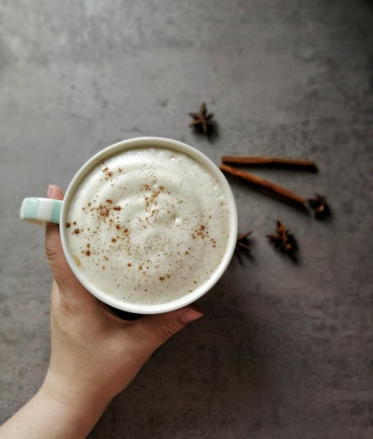 Eine Hand hält eine Tasse mit aufgeschäumter Milch. Auf der Oberfläche im Hintergrund sind Zimtstangen und Gewürznelken zu sehen.