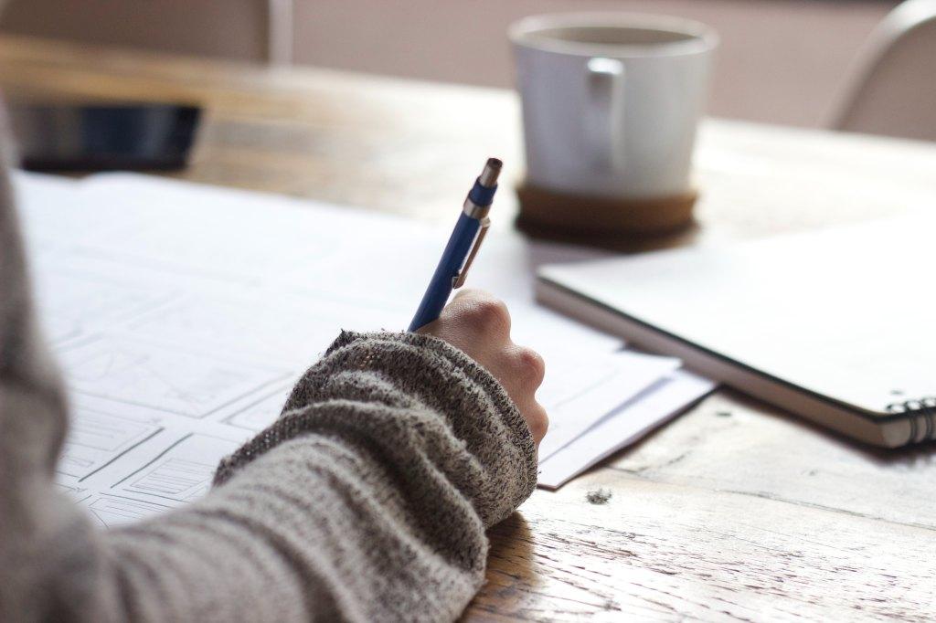 Eine Person hält einen Stift in der Hand und schreibt auf eines von vielen Blättern auf einem Schreibtisch.