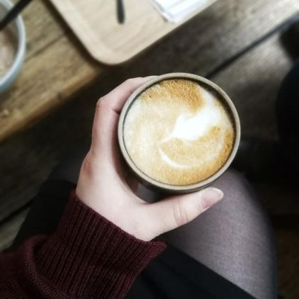 Eine Hand, die einen Kaffeebecher hält.