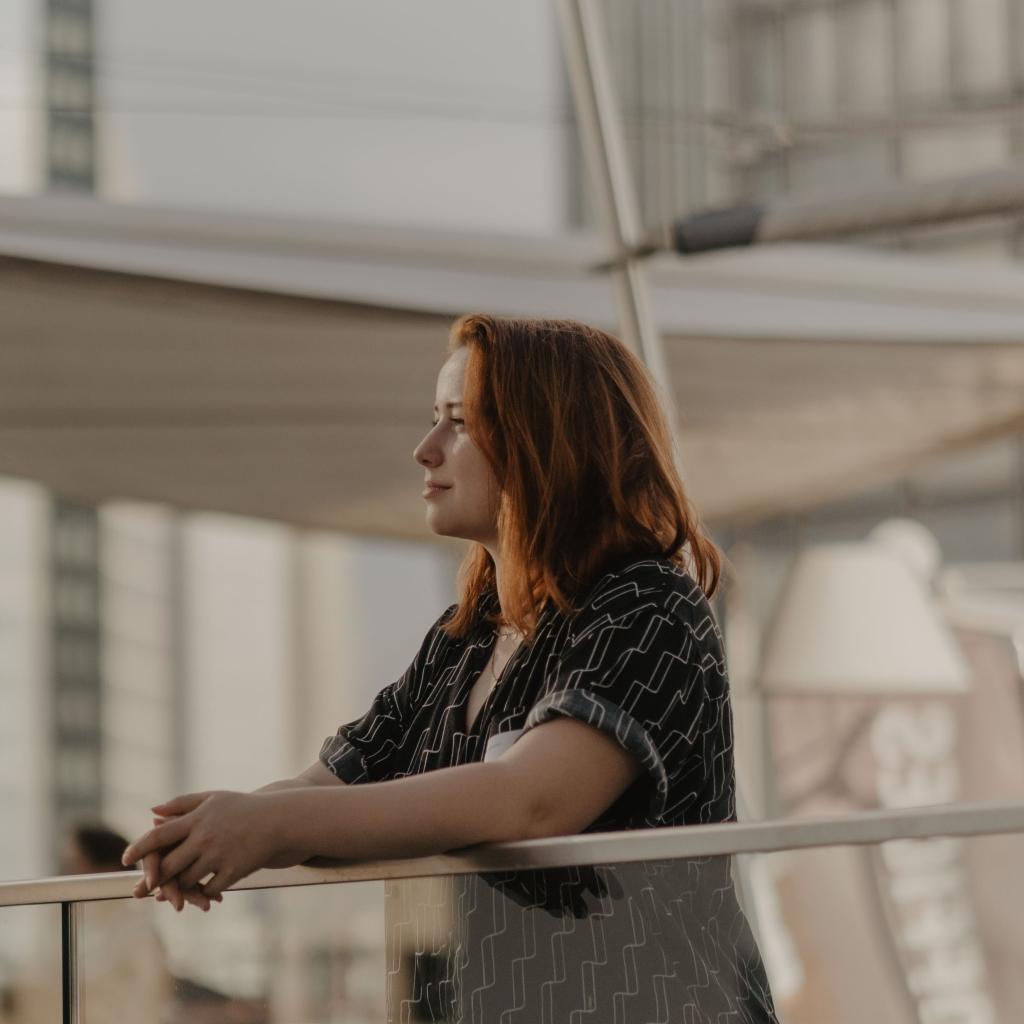 Eine Frau, Sirona Viola, stützt sich auf einem Geländer und blickt in die Ferne.