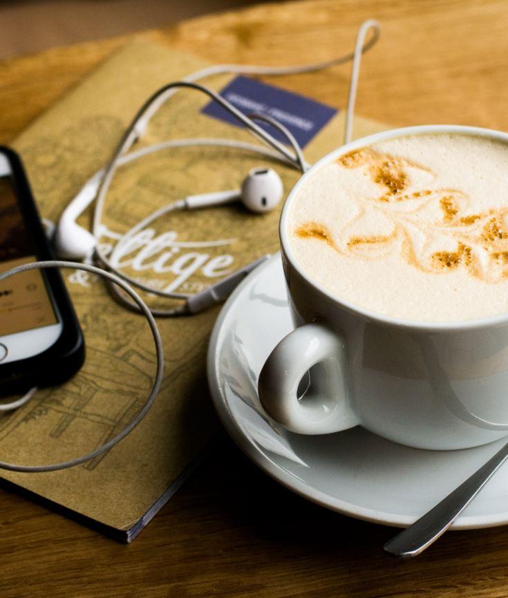 Ein Foto einer Kaffeetasse und eines Smartphones mit Kopfhörern - denn Podcasts kann man überall hören.