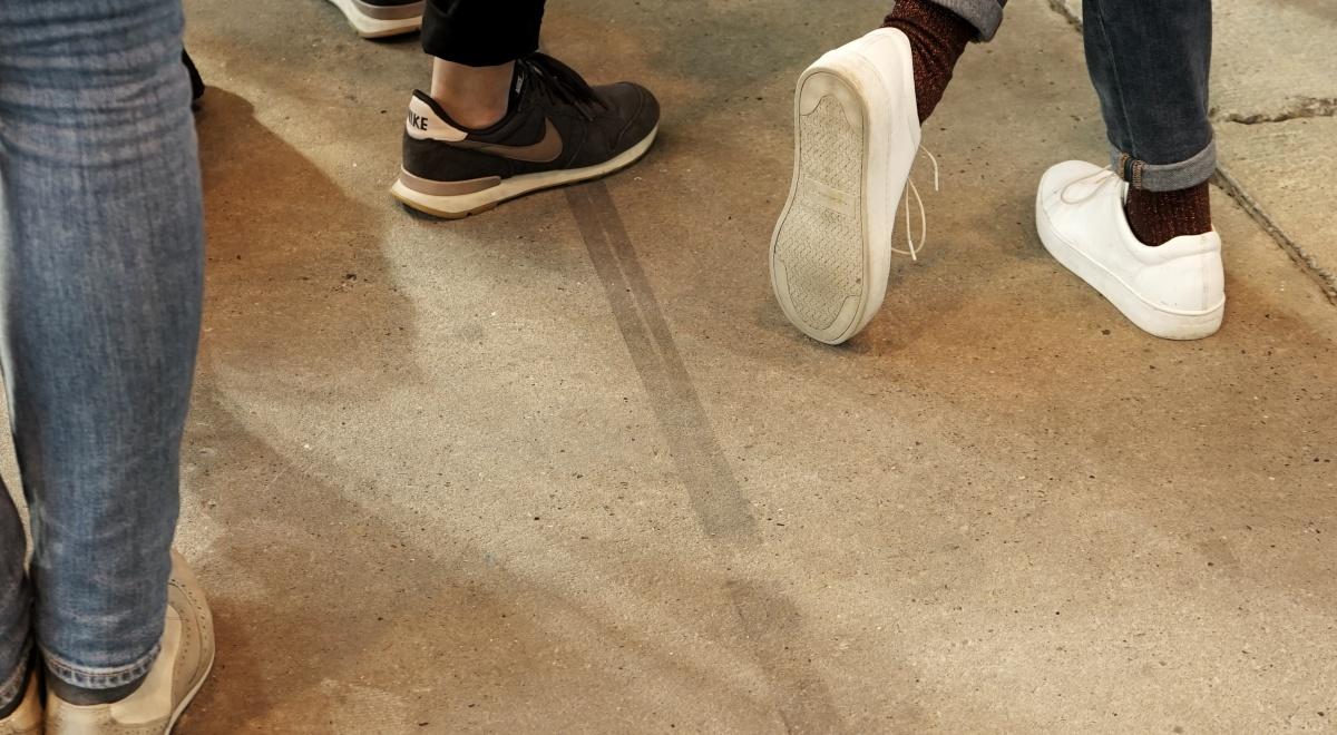 Mehrere Personen stehen beisammen, das Foto zeigt die Füße der Gruppe. Eine Person hat die Beine überkreuz.