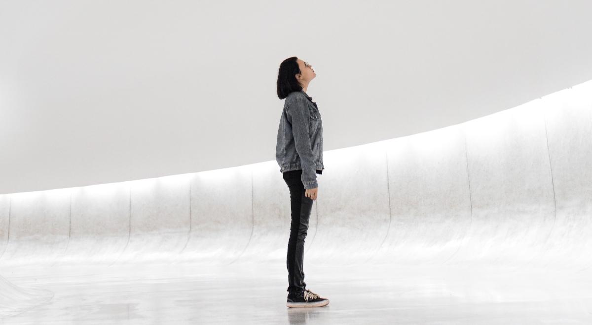 Eine junge Frau vor einem hellen Hintergrund blickt nach oben.